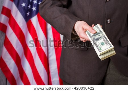 Businessman holding dollars beside flag. US flag, person and money. Our country our rules. I suggest you join us. - stock photo