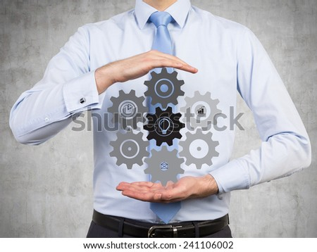 businessman holding drawing cogs and gears - stock photo
