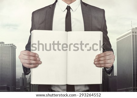 Businessman holding empty book sheet on cityscape background - stock photo