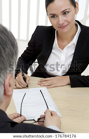 Businessman holding eyes glasses is waiting for  a woman signature, the women's hands can be seen about to sign.  - stock photo
