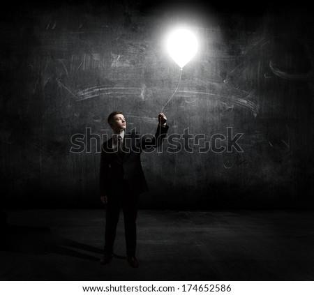 businessman holding flying light bulb - stock photo