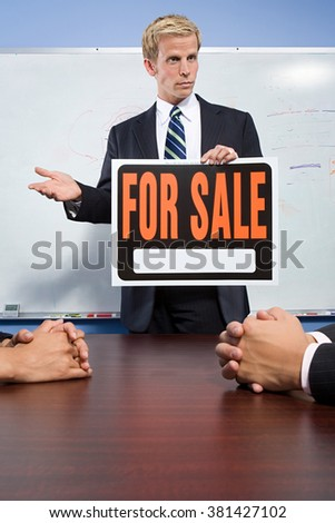Businessman holding for sale sign - stock photo