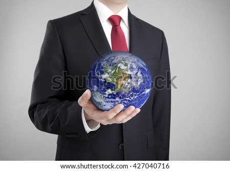 Businessman holding globe. Clipping path included. Earth image provided by Nasa. - stock photo