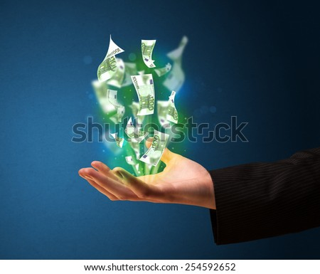 Businessman holding glowing paper moneys in his hand - stock photo