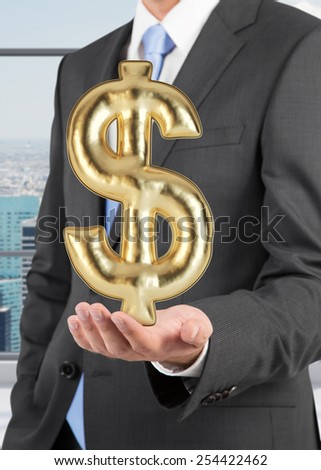 businessman holding gold ballon in form dollar