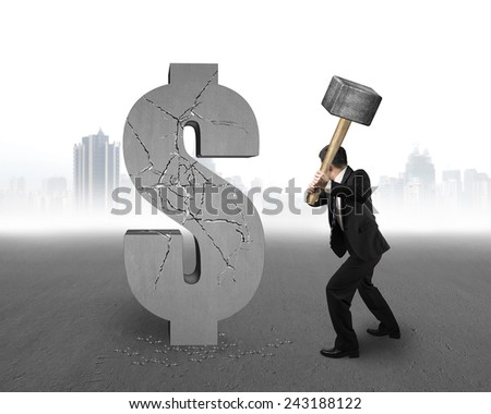businessman holding hammer hitting cracked dollar sign with gray cityscape concrete floor background - stock photo
