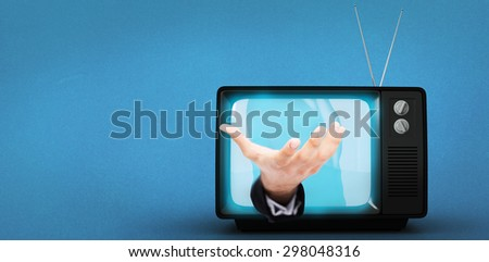 Businessman holding hand out in presentation against blue background