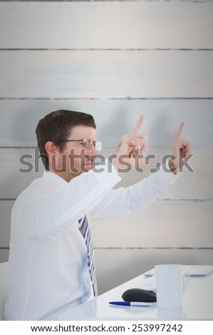 Businessman holding hands up at desk against wooden planks
