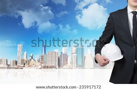 businessman holding helmet on skyscraper background - stock photo