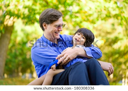 Businessman holding his disabled son on grass. Child has cerebral palsy. - stock photo