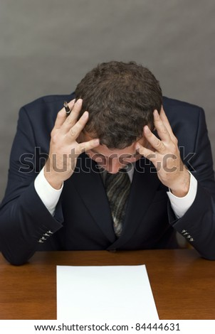 Businessman holding his head - stock photo