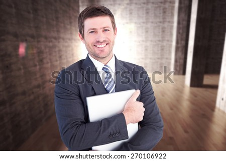 Businessman holding his laptop tightly against abstract room - stock photo