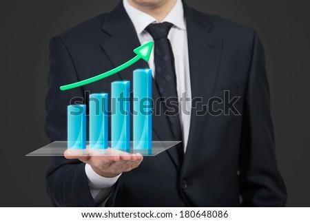 Businessman holding hologram chart - stock photo