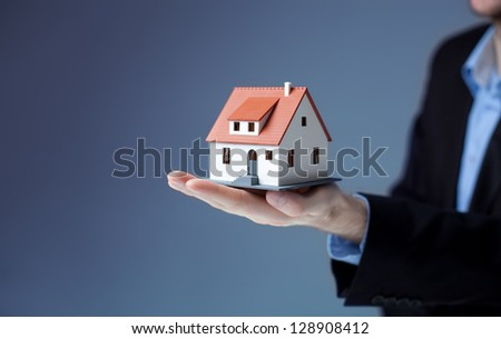 Businessman holding home model. Loan concept - stock photo