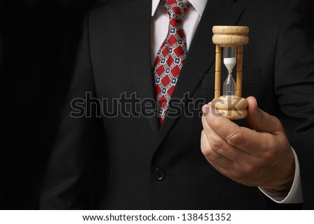 businessman holding hourglass towards camera with space for copy