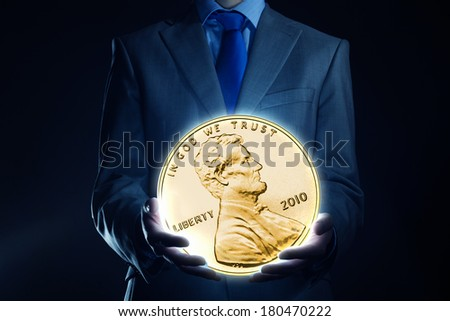 Businessman holding huge cent coin in hand - stock photo