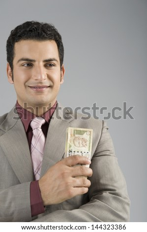 Businessman holding Indian five hundred rupee banknotes - stock photo