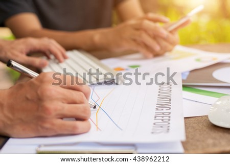 businessman Holding key using his laptop,stock chart,cellphone, close up