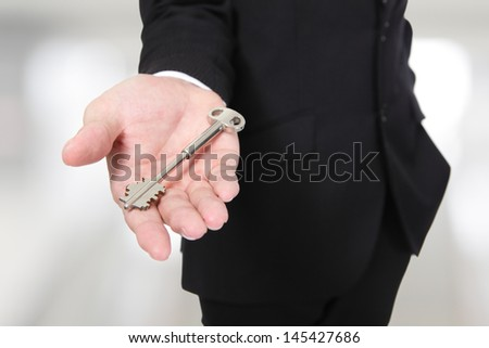 businessman holding keys isolated on gray background,concept for business or real estate,  asian male