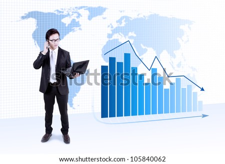 Businessman holding laptop with a world map and graph with arrow pointing downward financial crisis - stock photo