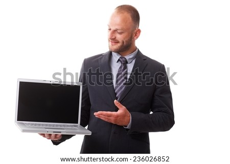 Businessman holding laptop with blank screen, showing laptop with other hand, smiling. - stock photo