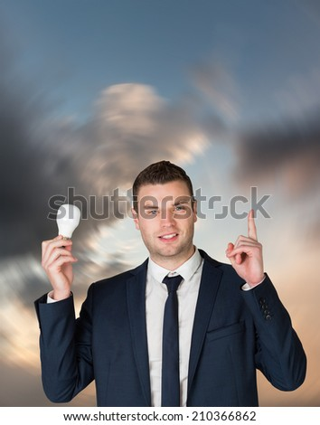 Businessman holding light bulb and pointing against blue and orange sky with clouds