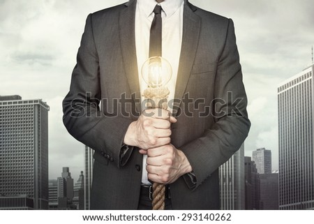 Businessman holding light bulb on cityscape background - stock photo
