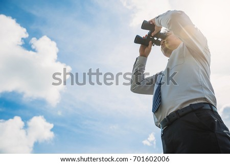 Businessman holding looking and using binoculars with blue sky . Businessman with binoculars spying on sky background.