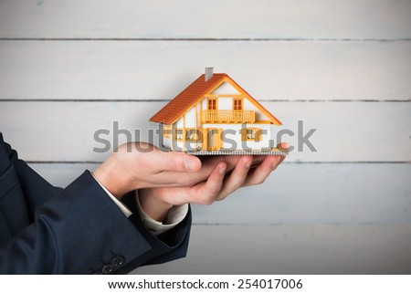 Businessman holding miniature house model against painted blue wooden planks - stock photo