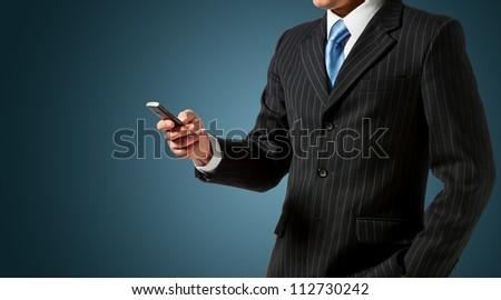 Businessman holding mobile phone - stock photo