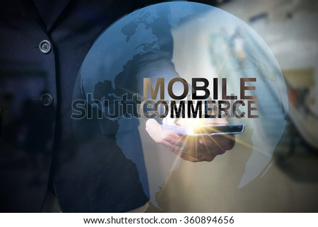 Businessman holding mobile phone with MOBILE COMMERCE text on virtual screen. Internet concept. Business concept. Business idea - stock photo