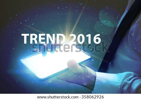 businessman holding mobile phone with TREND 2016 text on virtual screen. Internet concept. Business concept. Business idea - stock photo
