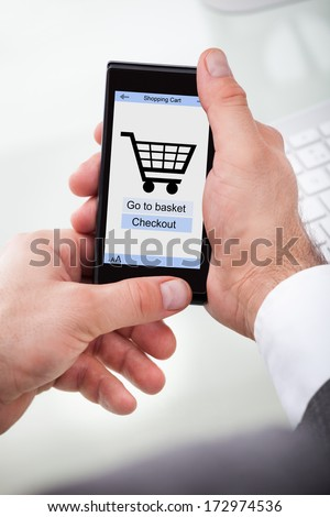Businessman Holding Mobile With Online Shopping Application On A Screen - stock photo