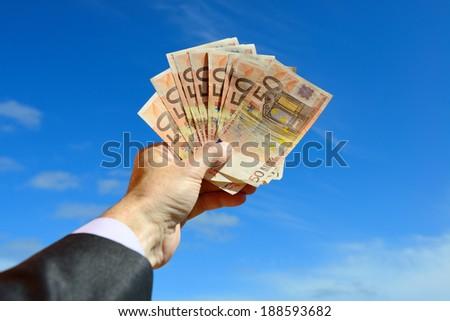 Businessman holding money- Euro, over blue sky - stock photo