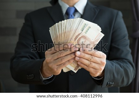 Businessman holding money thai baht