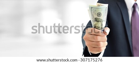 Businessman holding money,   united states dollar (USD) bills, on blur white gray background  - financial and investment panoramic background concept - stock photo