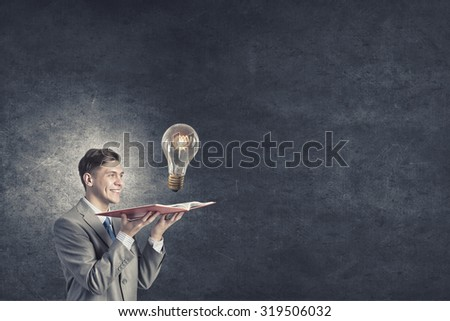 Businessman holding opened book with glass glowing light bulb