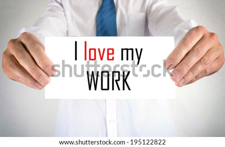 Businessman holding or showing card with I love my work text - stock photo