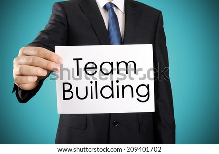 Businessman holding or showing card with Team Building text