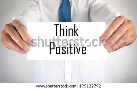 Businessman holding or showing card with think positive text - stock photo