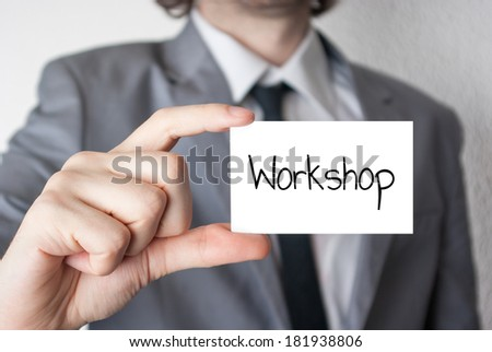 Businessman holding or showing card with Workshop text - stock photo