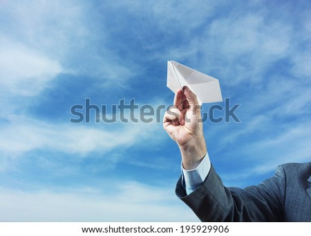 Businessman holding paper plane in his hand - stock photo