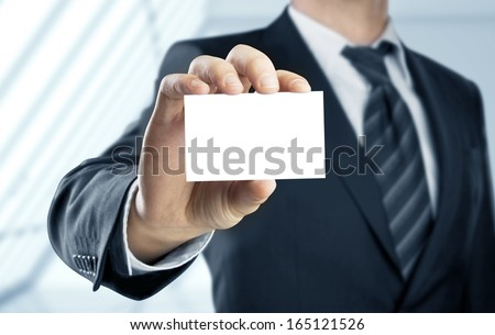 businessman holding paper visit card - stock photo