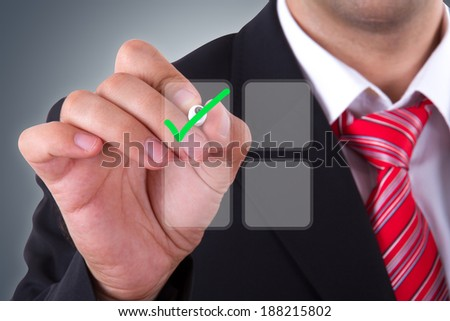 Businessman holding pen and checking check mark of list on digital screen. - stock photo