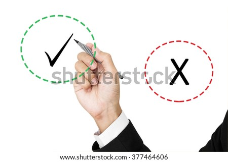 Businessman holding pen chosen between correct and incorrect marks, isolated on white background - stock photo