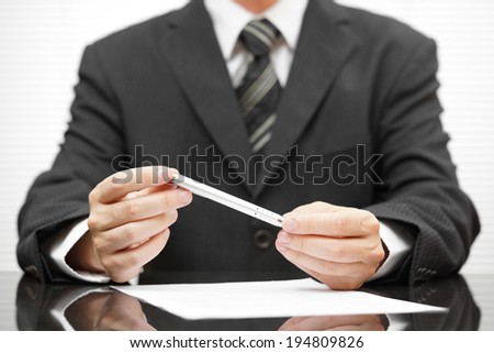 businessman holding pen over proposed contract and thinking about deal to make - stock photo