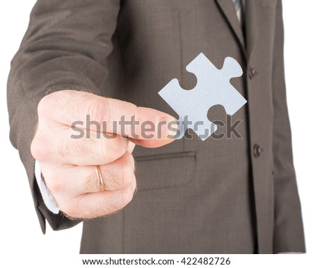 Businessman holding piece of grey puzzle isolated on white background