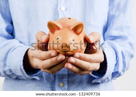 businessman holding piggy bank savings - stock photo