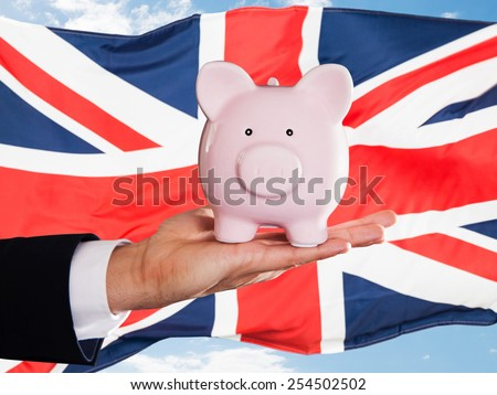 Businessman Holding Piggybank In Front Of British Flag - stock photo