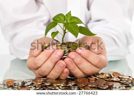 Businessman holding plant sprouting from a handful of coins - good investment and money concept - stock photo